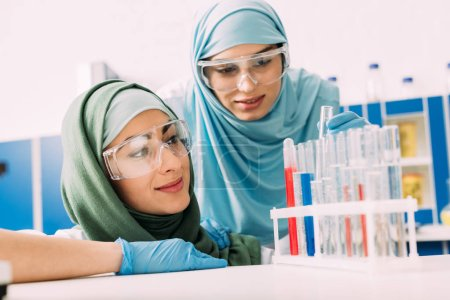 Photo for Female muslim scientists in goggles looking at reagents in glass test tubes during experiment in chemical lab - Royalty Free Image