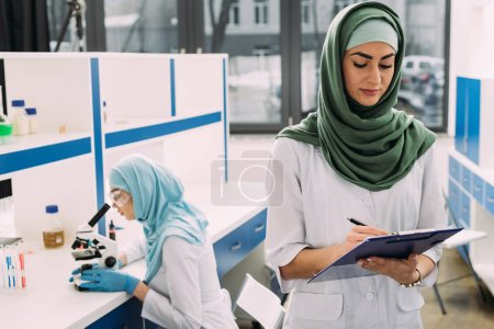 Photo for Concentrated female muslim scientists using microscope and writing in clipboard during experiment in chemical laboratory - Royalty Free Image