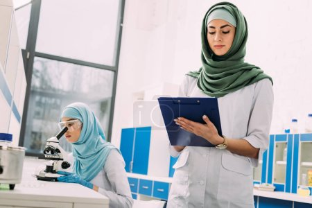 concentrated female muslim scientists using microscope and writing in clipboard during experiment in chemical laboratory