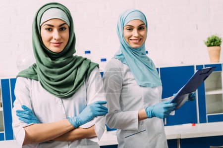 Photo for Beautiful female muslim chemists in hijab with arms crossed and clipboard looking at camera in laboratory - Royalty Free Image