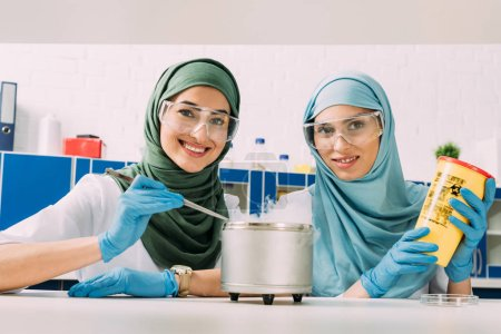 Photo for Female muslim scientists in goggles looking at camera while experimenting with dry ice in chemical laboratory - Royalty Free Image