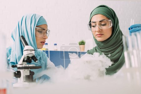 Photo for Female muslim scientists in goggles experimenting with microscope and dry ice in chemical laboratory - Royalty Free Image