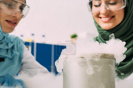 Photo for Female muslim scientists in goggles experimenting with dry ice in chemical laboratory - Royalty Free Image