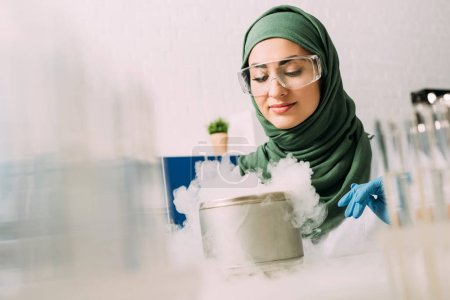 Photo for Female muslim scientist in goggles during experiment with dry ice in laboratory - Royalty Free Image