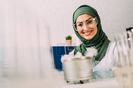 Photo for Smiling female muslim scientist looking at camera during experiment with dry ice in laboratory - Royalty Free Image
