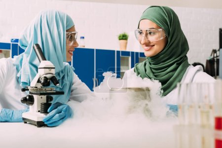 Photo for Smiling female muslim scientists experimenting with microscope and dry ice in chemical laboratory - Royalty Free Image