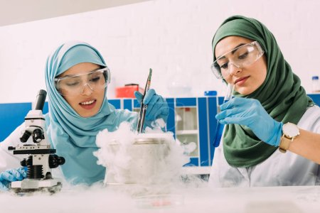 Photo for Female muslim scientists in hijab experimenting with microscope and dry ice in chemical laboratory - Royalty Free Image