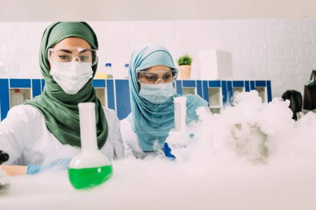 Photo for Focused female muslim scientists during experiment with dry ice in chemical laboratory - Royalty Free Image