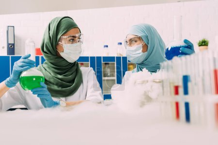 Photo for Female muslim scientists holding flasks while experimenting with dry ice in chemical laboratory - Royalty Free Image