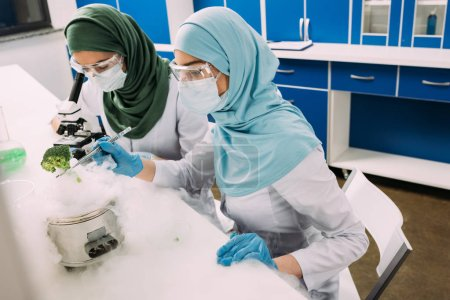 Photo for Female muslim scientists experimenting with dry ice and using microscope in chemical laboratory - Royalty Free Image