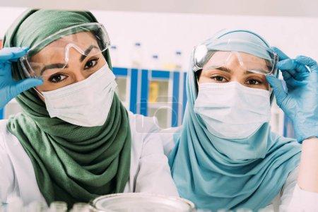 Photo pour Femmes chimistes musulmans en masques à usage médical et hijab en regardant la caméra en laboratoire - image libre de droit