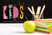 fresh apple, notebooks and color pencils on table with enjoy life while you are young and kids lettering on black