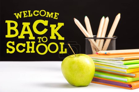 Photo for Fresh apple, notebooks and color pencils on table with welcome back to school  lettering on black - Royalty Free Image