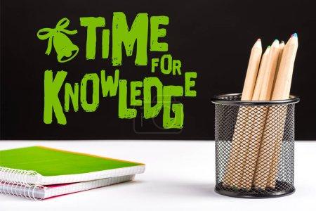 Photo pour Cahiers et crayons de couleur sur table avec le temps vert pour inscription connaissances et bell signent sur fond noir - image libre de droit