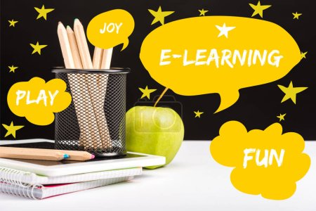 fresh apple, notebooks and color pencils on table with e-learning and joy words  in yellow speech bubbles and play and fun words in clouds with stars around on black