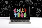 laptop on table with enjoy life while you are young and childhood lettering on screen with white space illustration on black