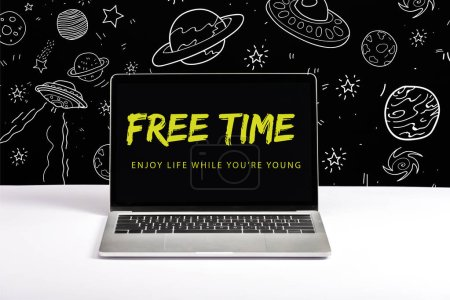 Photo for Laptop on table with enjoy life while you are young and free time lettering on screen with white galaxy illustration on black - Royalty Free Image