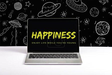 Photo pour Ordinateur portable sur la table à profiter de la vie pendant que vous êtes jeunes et lettrage de bonheur à l'écran avec une illustration de la galaxie blanche sur fond noir - image libre de droit