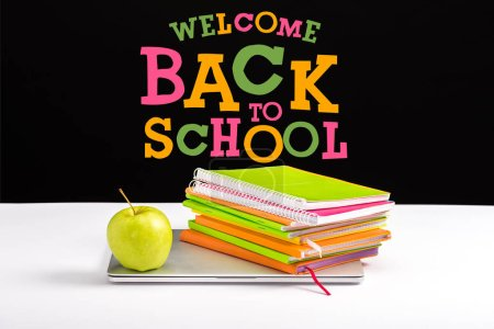 Photo for Closed laptop, green apple, notebooks and color pencils on desk with welcome back to school lettering on black - Royalty Free Image