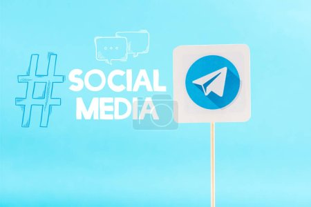 Photo pour Carte avec logo télégramme et lettrage sur les médias sociaux avec hashtag isolé sur bleu - image libre de droit