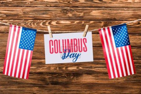 Photo pour Carte avec Columbus day inscription suspendue sur chaîne avec des épingles et des drapeaux américains sur fond en bois - image libre de droit