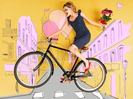 Photo pour Vue de dessus de jeune femme élégante heureuse avec bouquet de roses et vélo couché sur fond jaune avec illustration de rue de la ville - image libre de droit