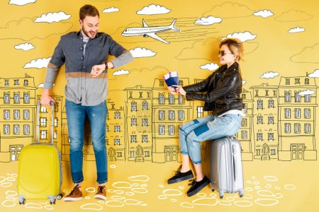 Photo for Happy woman holding passports and tickets while man with suitcase checking time with city and airplane illustration on yellow background - Royalty Free Image