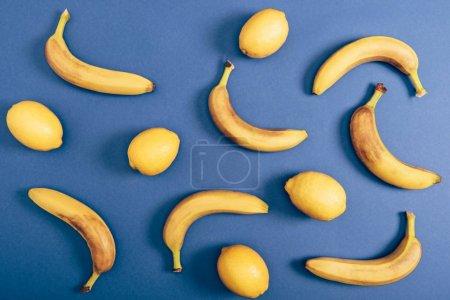 Foto de Composición de alimentos con limones y plátanos maduros aislados sobre fondo azul - Imagen libre de derechos
