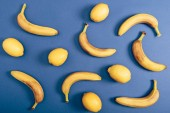 "Постер, картина, фотообои ""Food composition with lemons and ripe bananas lying isolated on blue background"""