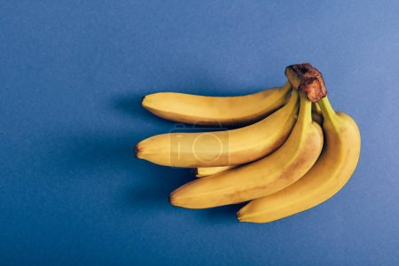 Photo for Top view of ripe bunch of delicious bananas on blue background - Royalty Free Image