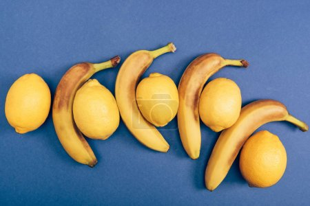 Foto de Vista superior de limones brillantes y amarillos con plátanos sobre fondo azul - Imagen libre de derechos