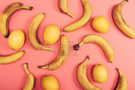 Photo for Top view of bright juicy lemons and yellow bananas on coral background - Royalty Free Image