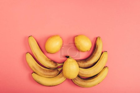 Photo for Flat lay with food composition of yellow juicy bananas and fresh lemons on coral background - Royalty Free Image