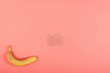 Foto de Vista superior del plátano maduro, brillante y amarillo sobre fondo de coral colorido con espacio de copia - Imagen libre de derechos