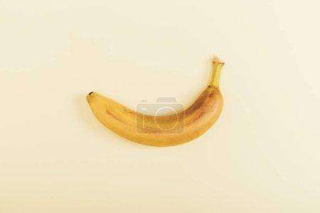 Foto de Top view of fresh bright and yellow banana on light beige background - Imagen libre de derechos