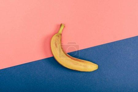 Foto de Top view of fresh yellow banana on multicolored coral and blue background - Imagen libre de derechos