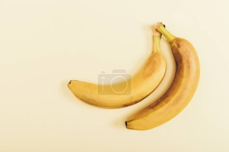 Photo for Top view of delicious and yellow bananas on light beige background - Royalty Free Image