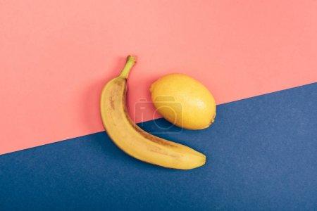 Foto de Top view of yellow banana and juicy lemon on multicolored coral and blue background - Imagen libre de derechos