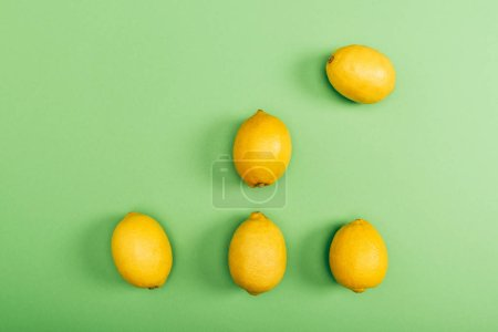 Photo pour Vue supérieure des citrons frais et jaunes sur le fond vert coloré - image libre de droit