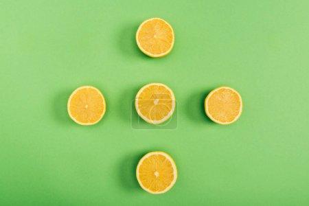 Photo pour Vue supérieure des citrons coupés jaunes et délicieux sur le fond vert coloré - image libre de droit