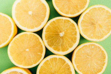 Photo for Close up view of bright yellow cut lemons on colorful green background - Royalty Free Image