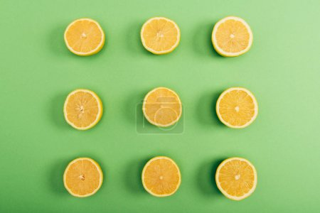 Photo for Top view of fresh and yellow cut lemons on colorful green background - Royalty Free Image