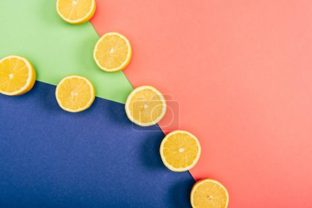 Photo for Top view of juicy, fresh and yellow cut lemons on multicolored background - Royalty Free Image