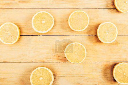 Photo for Top view of juicy, fresh and yellow cut lemons on wooden table background - Royalty Free Image