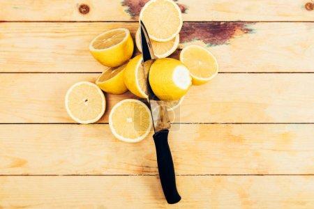 Photo pour Vue supérieure des citrons coupés frais et jaunes avec le couteau sur le fond en bois de table - image libre de droit