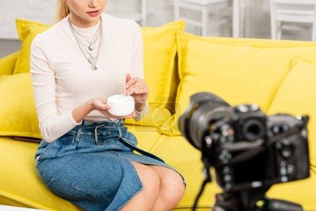 Photo pour Vue recadrée du blogueur en jupe en denim tenant crème cosmétique devant la caméra vidéo - image libre de droit