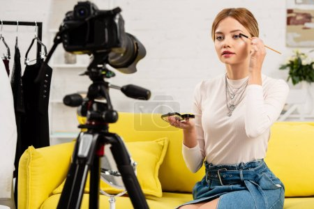 Photo for Beauty blogger doing makeup in front of video camera at home - Royalty Free Image