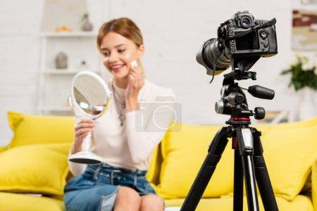 Photo pour Foyer sélectif de sourire blogueur beauté avec miroir en utilisant des cosmétiques décoratifs devant la caméra vidéo - image libre de droit