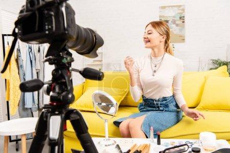 Photo pour Blogueur de beauté souriant retenant le parfum devant la caméra vidéo - image libre de droit