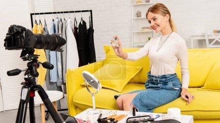 Photo pour Blogueur beauté souriant montrant le parfum devant la caméra vidéo - image libre de droit